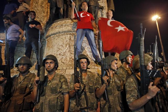 Tureckí vojaci stoja pred stúpencami prezidenta Recepa Tayyipa Erdogana počas protestu v Istanbule na námestí Taksim v sobotu 16. júla 2016