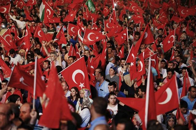 Na snímke ľudia mávajú tureckými zástavami na zhromaždení na podporu tureckej vlády na istanbulskom námestí Taksim večer 18. júla 2016. Stovky ľudí sa v noci nadnes už štvrtýkrát zhromaždili na námestiach veľkých tureckých miest, aby po neúspešnom pokuse o vojenský prevrat, ku ktorému došlo 15. júla, vyjadrili podporu vláde