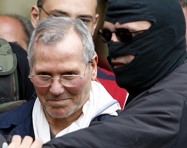 Na archívnej snímke zamaskovaný policajt doprevádza zatknutého mafiánskeho šéfa Bernarda Provenzana (vľavo)