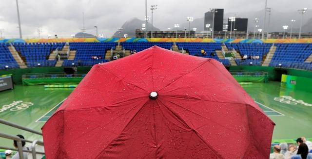 Fanúšik čaká pod dáždnikom v hľadisku centrálneho kurtu po tom, ako sa pre dážď posunuli tenisové zápasy na OH 2016 v Rio de Janeiro