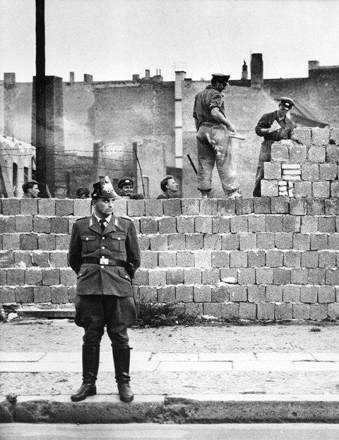 Na archívnej snímke zo 7. októbra 1961 berlínsky policajt stráži robotníkov pri stavbe múru