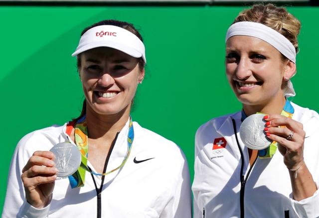 Švajčiarske tenistky Timea Bacsinszká (vpravo) a Martina Hingisová pózujú so striebornou medailou po prehre vo finálovom zápase ženskej štvorhry proti ruskému deblovému páru Jekaterina Makarovová, Jelena Vesninová na OH 2016 v Rio de Janeiro