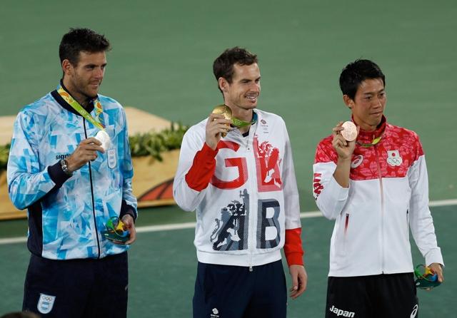 Britský tenista Andy Murray (uprostred) pózuje so zlatou olympijskou medailou po výhre nad Argentínčanom Juanom Martinom del Potrom (vľavo) vo finále mužskej dvojhry na OH v Riu de Janeiro.  Bronz získal Japonec Kei Nišikori (vpravo), ktorý v boji o tretie miesto porazil Španiela Rafaela Nadala