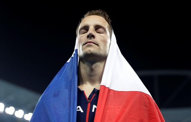 Francúzsky atlét Renaud Lavillenie má na hlave národnú vlajku po zisku striebornej medaily, ktorú získal v skoku o žrdi na OH 2016 v Riu de Janeiro