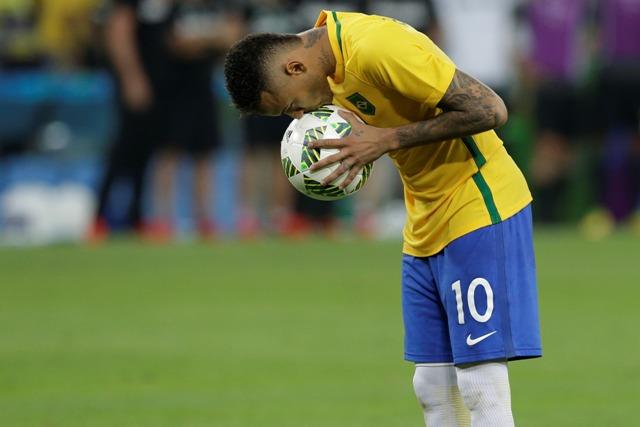 Brazílsky futbalista Neymar bozkáva loptu pred rozhodujúcou penaltou vo finále proti Nemecku na OH v Riu de Janeiro