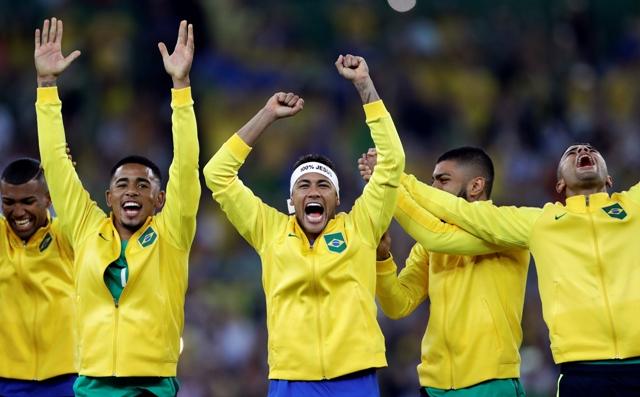 Brazílsky futbalista Neymar (uprostred) oslavuje so spoluhráčmi zisk olympijskej zlatej medaily na OH v Riu de Janeiro