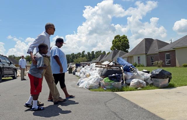 Americký prezident Barack Obama kráča s rodinou počas prehliadky oblasti postihnutej povodňami v Castle Place pri Baton Rouge, v americkom štáte Louisiana
