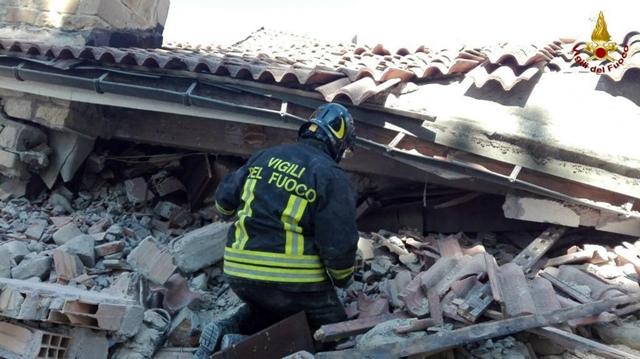 Hasič prehľadáva trosky zrútenej budovy po zemetrasení v meste Amatrice, v centrálnom Taliansku