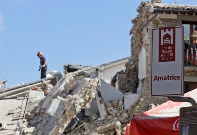 Hasič stojí na sutinách domu v meste Amatrice po otrasoch v strednom Taliansku