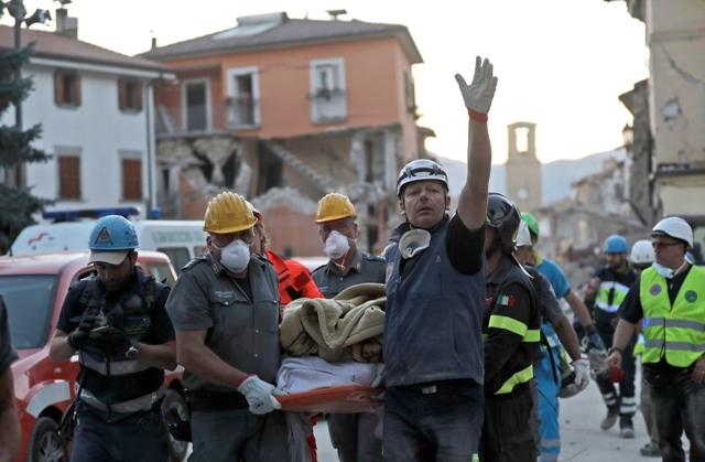 Záchranári vynášajú na nosidlách  telo pri prehľadávaní trosiek zrútenej budovy po zemetrasení v meste Amatrice, v centrálnom Taliansku Foto:TASR/AP-Alessandra Tarantino