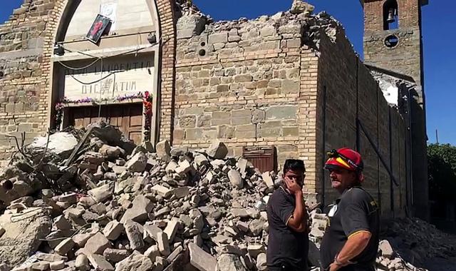 Na snímke z videa hasiči stoja pri troskách zrúteného kostola po zemetrasení v meste Villa San Lorenzo a Flaviano pri Amatrice v centrálnom Taliansku