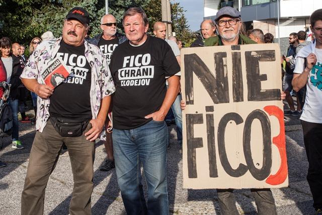 Na snímke protestujúci s novinami, ktoré sa rozdávali počas 10. protestu proti zlodejom v politike pred luxusným komplexom Bonaparte