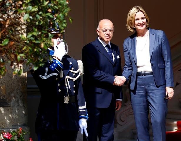 Francúzsky minister vnútra Bernard Cazeneuve (v strede) víta svoju britskú rezortnú partnerku Amber Ruddovú počas ich stretnutia v Paríži