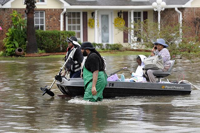 dobrovoľníci loďka ťahanie evakuovaná žena dieťa zaplavená ulica Baton Rouge