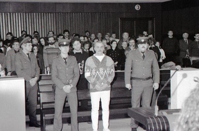 Na snímke z roku 1992 obžalovaní Ján Molnár (uprostred v popredí) a Ľubor Masár (uprostred v pozadí) stoja pri čítaní rozsudku
