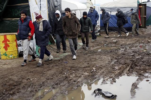Na snímke migranti kráčajú v utečeneckom tábore pri meste Calais