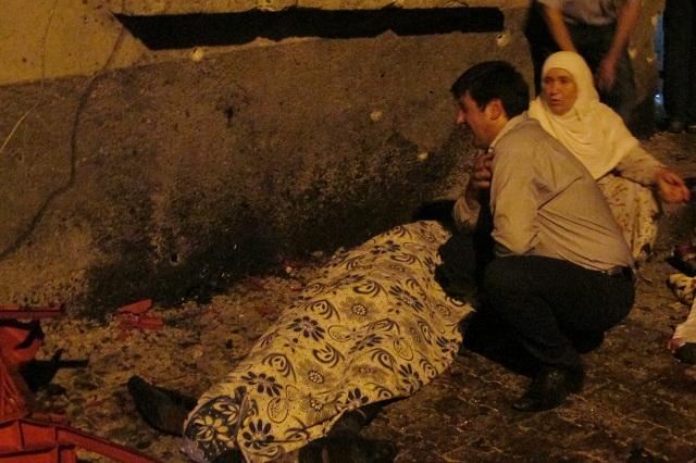 Muž narieka nad zakrytým telom obete po explózii v tureckom Gazientape 20. augusta 2016
