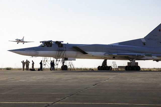 Na snímke z 15. augusta 2016 stojí ruský nadzvukový bombardér s dlhým doletom Tu-22M3 na letisku v iránskom Hamedane, ďalší stroj Tu-22M3 (vľavo) práve pristáva. Ruské letectvo využíva iránske základne na vzlety ťažkých bombardérov na ciele IS v Sýrii