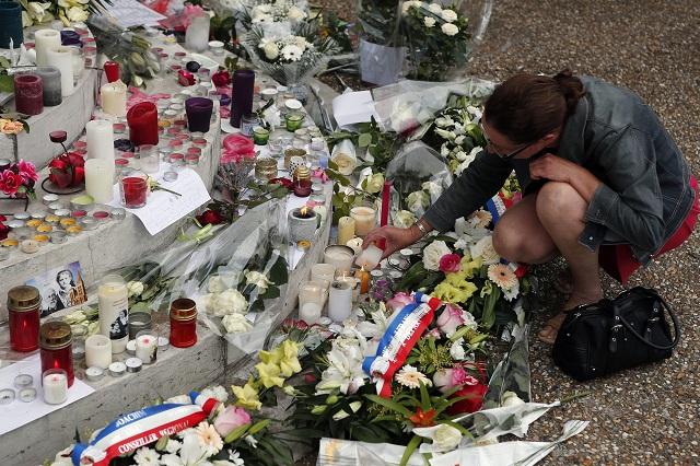 Žena zapaľuje sviečku pri pamätníku pred radnicou v Saint-Etienne-du-Rouvray 27. júla 2016 po útoku na kostol, pri ktorom zahynul kňaz
