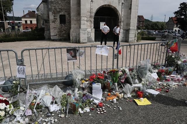 Kvety a sviečky položené pri pamätníku pred kostolom v Saint-Etienne-du-Rouvray 28. júla 2016, v ktorom po útoku islamistov zahynul kňaz