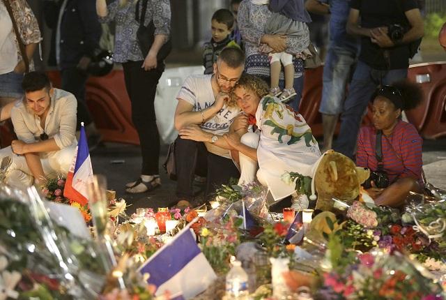 Na archívnej snímke ľudia pokladajú kvety a zapaľujú sviečky neďaleko miesta, na ktorom nákladné auto vrazilo do davu ľudí počas sviatku Dňa Bastily