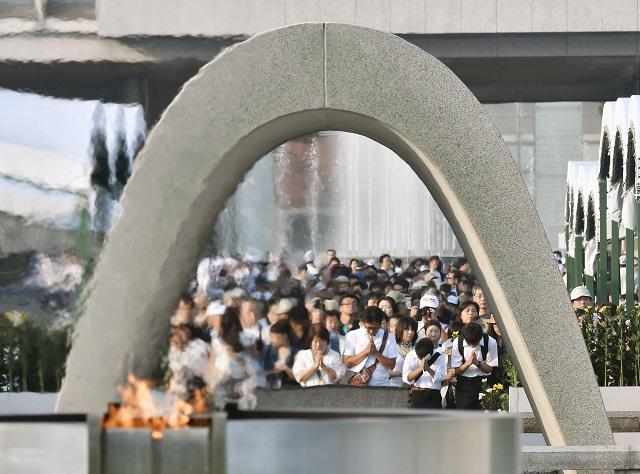 Ľudia sa modlia za obete zhodenia atómovej bomby pre pamätníkom v Parku mieru pri príležitosti 71. výročia zhodenia atómovej bomby na mesto Hirošima 6. augusta 2016