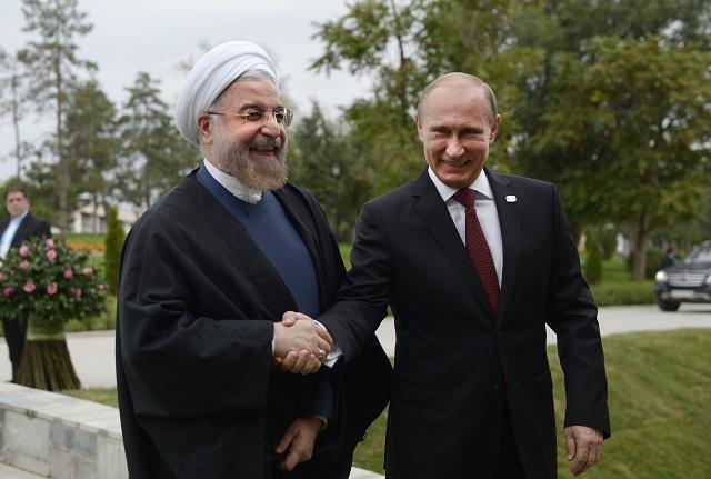 na archívnej snímke si ruský prezident Vladimir Putin (vpravo) podáva ruku so svojím iránskym partnerom Hassanom Ruháním