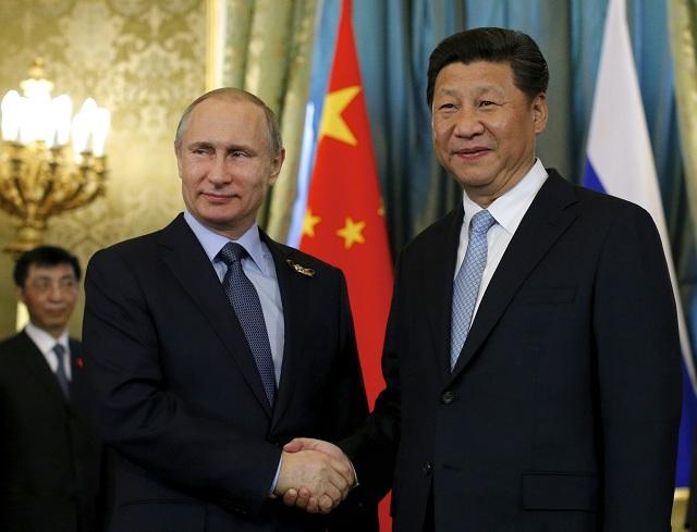 Na archívnej snímke ruský prezident Vladimir Putin (vľavo) víta čínskeho prezidenta Si Ťin-pchinga v moskovskom Kremli