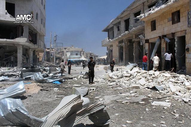 Sýrski obyvatelia skúmajú škody po leteckých útokoch na trh v Atarebe, západne od rozdeleného sýrskeho mesta Aleppo