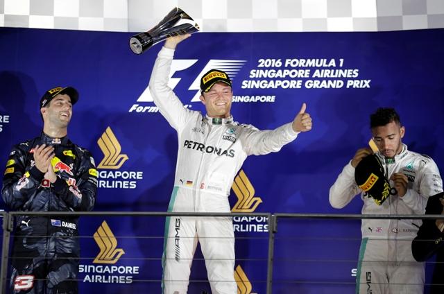 Nemecký jazdec tímu Mercedes Nico Rosberg (uprostred) sa teší po triumfe v nočnej Veľkej cene Singapuru seriálu majstrovstiev sveta formuly 1 v Singapure
