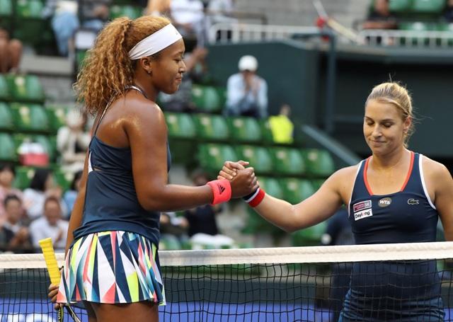 Japonská tenistka Naomi Osaková (vľavo) podáva ruky Slovenke Dominike Cibulkovej po výhre v 2. kole ženskej dvojhry na tenisovom turnaji WTA v Tokiu