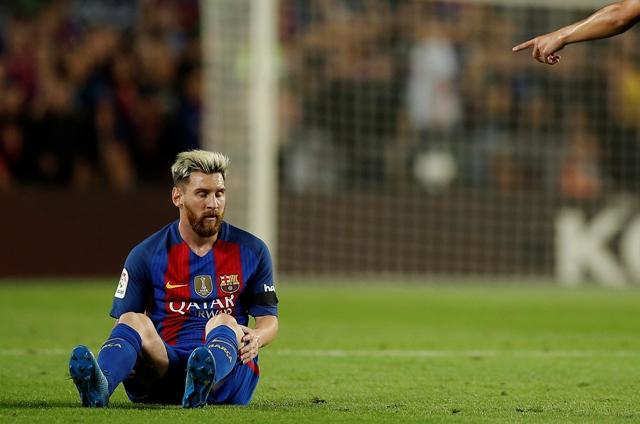 Futbalista FC Barcelony Lionel Messi sedí na trávniku v šlágri 5. kola španielskej ligy FC Barcelona - Atletico Madrid