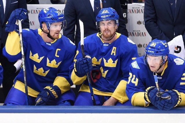 Na snímke hokejisti Švédska súrodenci Henrik Sedin (vľavo), Daniel Sedin a spoluhráč Carl Soderberg