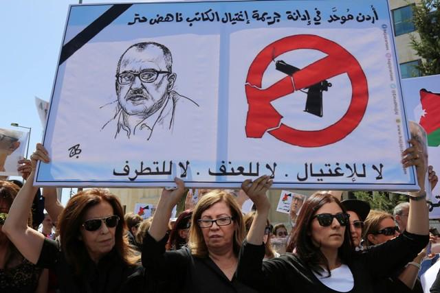 """Príbuzní zavraždeného spisovateľa Náhida Hattara držia transparent s nápisom """"Nie extrémizmu, nie násiliu,"""" či """"preč s vládou"""" počas protestu pred úradom vlády v jordánskom Ammáne"""