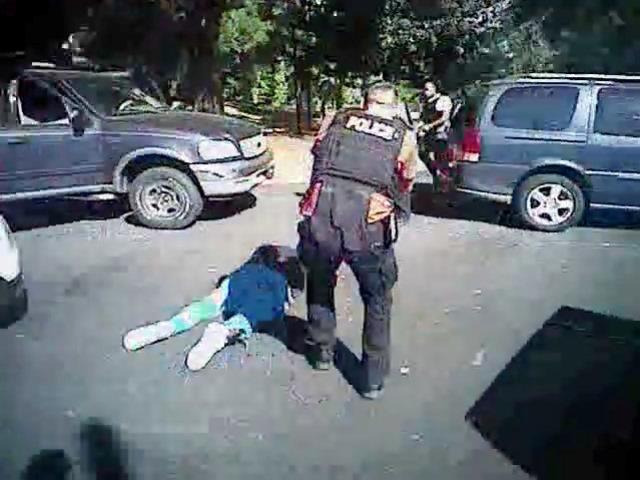 Na videosnímke zverejnenej políciou policajt stojí nad ležiacim Keithom Lamontom Scottom v Charlotte