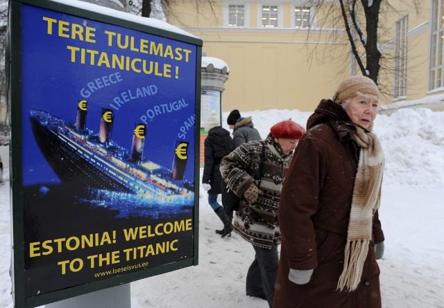 """Obyvatelia estónskeho Tallinnu prechádzajú okolo plagátu s motívom potápajúceho sa Titaniku a s nápisom """"Estónsko! Vitaj na Titaniku"""""""