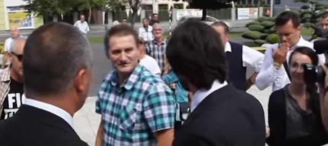 Na snímke z videa muž stojí oproti ministrovi a nadáva mu