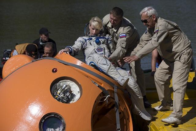 Na snímke zamestnanci ruského vesmírneho tréningového strediska pomáhajú americkej astronautke NASA Kathleen Rubinsovej nastúpiť do vesmírnej kapsule počas simulácie pristátia na vodnej hladine v tréningovom stredisku v Noginsku