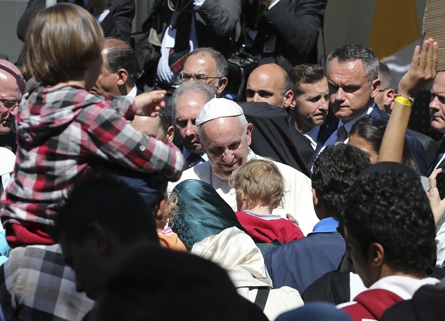 Na snímke v strede pápež František  počas návštevy migrantov v tábore Moria na gréckom ostrove Lesbos