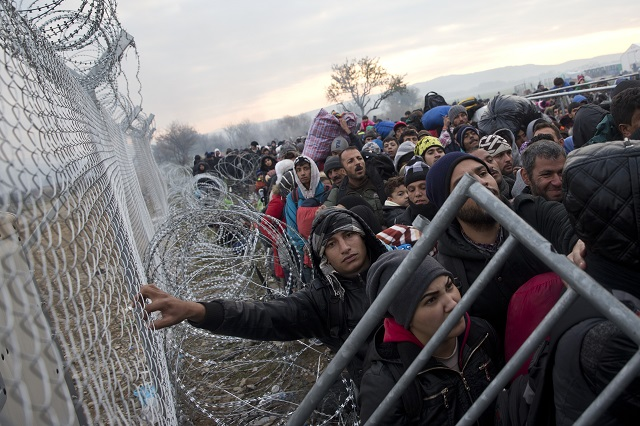 Ilustračné foto: Na snímke migranti a utečenci čakajú pri plote na grécko-macedónskej hranici v snahe prejsť do Macedónska v Idomeni