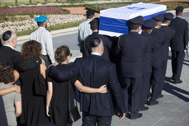 Rodinní príslušníci kráčajú za príslušníkmi čestnej stráže, ktorí nesú rakvu bývalého izraelského prezidenta Šimona Peresa na nádvorí izraelského parlamentu (Knesetu) v Jeruzaleme 30. septembra 2016. Izrael sa lúči so svojím zosnulým exprezidentom Šimonom Peresom, ktorého dnes pochovajú na Národnom cintoríne Mount Herzel v Jeruzaleme