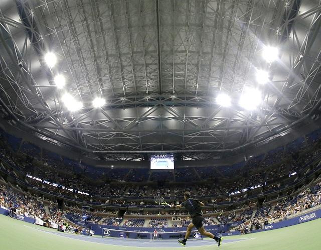Španiel Rafael Nadal (v popredí) odvracia úder Taliana Andreasa Seppiho v zápase 2. kola mužskej dvojhry pod premiérovo zatiahnutou strechou na hlavnom kurte Štadióna Arthura Ashea na granslamovom turnaji US Open v stredu 31. augusta 2016