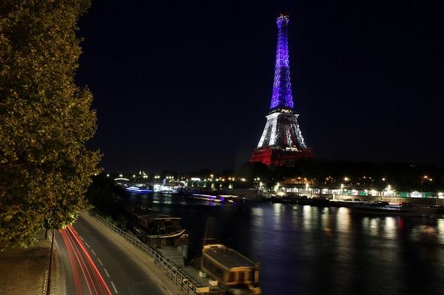 Pohľad na Eiffelovu vežu, ktorá je vysvietená vo farbách francúzskej vlajky v rámci solidarity za obete teroristického útoku z francúzskeho Nice