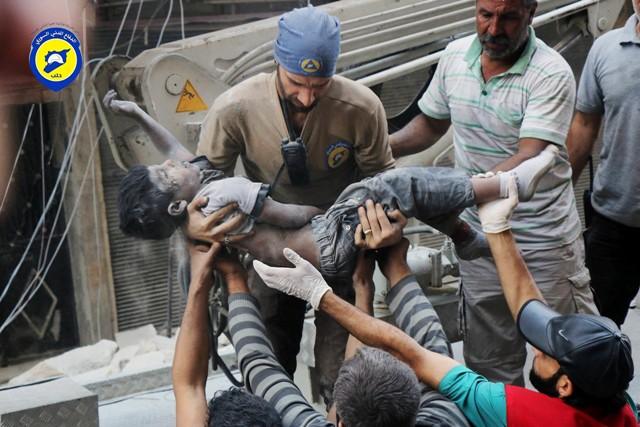 Na snímke zo Sýrskej civilnej obrany Biele helmy záchranári vynášajú telo chlapca z trosiek zničenej budovy po leteckých útokoch v sýrskom meste Aleppo