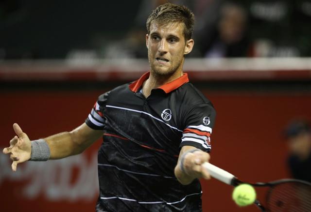 Slovenský tenista Martin Kližan odvracia loptičku Portugalčanovi Joaovi Sausovi v 1. kole na turnaji ATP v Tokiu
