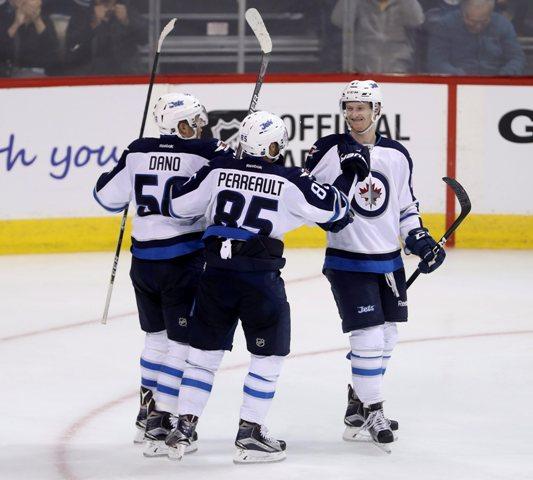Hráči Jets - slovenský útočník Marko Daňo (vľavo) a Mathieu Perrarult gratulujú spoluhráčovi Kyleovi Connorovi ku gólu v prípravnom dueli Ottawa Senators - Winnipeg Jets pred štartom novej sezóny zámorskej NHL