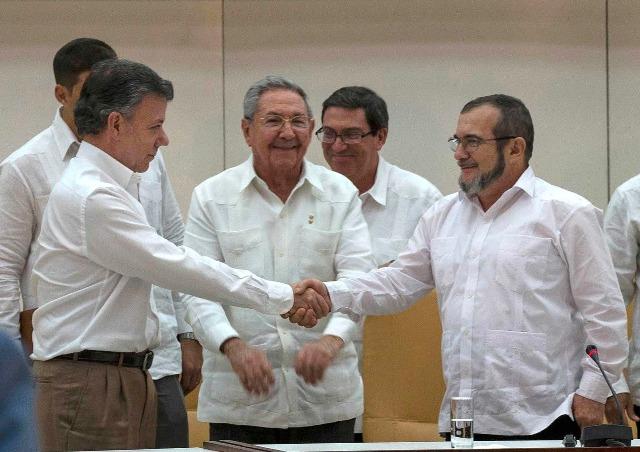 """Na archívnej snímke z 23. septembra 2015 v Havane kolumbijský prezident  Juan Manuel Santos (vľavo) a veliteľ Revolučných ozbrojených síl Kolumbie (FARC) Timoleon Jimenez, známy ako """"Timošenko"""" si podávajú ruky, uprostred sa usmieva kubánsky prezident Raúl Castro. Nositeľom Nobelovej ceny za mier za rok 2016 sa stal kolumbijský prezident Juan Manuel Santos"""