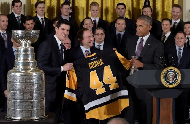 Na snímke americký prezident Barack Obama (vpravo v popredí), kapitán Pittsburghu Penguins Sidney Crosby (vľavo) a komisár NHL Gary Bettman pózujú s dresom klubu počas prijatia hokejistov Pittsburghu Penguins v Bielom dome vo Washingtone