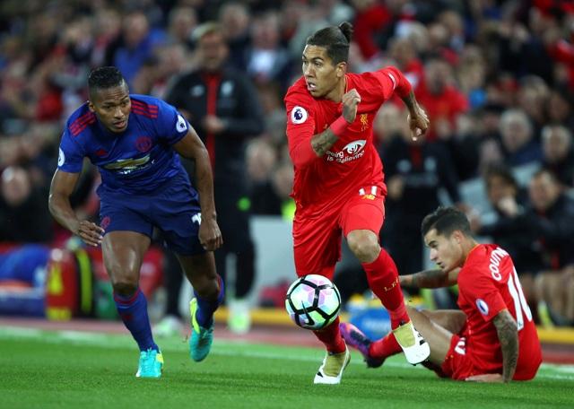 Na snímke druhý sprava hráč Liverpoolu Roberto Firmino a vľavo hráč United Eric Bailly v dohrávanom zápase 8. kola anglickej futbalovej Premier League FC Liverpool – Manchester United