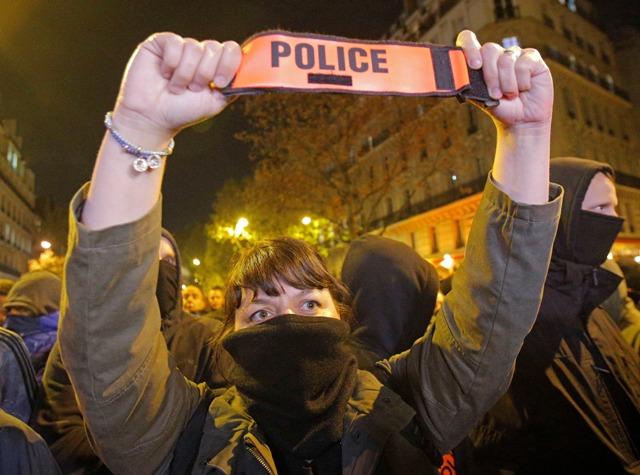 Maskovaná policajtka počas demonštrácie na Champs Elysees v Paríži